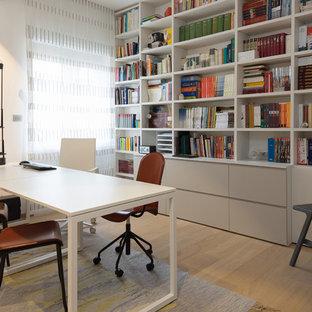Immagine di un piccolo studio minimal con libreria, pareti bianche, parquet chiaro, scrivania autoportante e pavimento beige