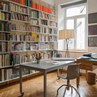 Idéer för ett mellanstort nordiskt hemmabibliotek, med vita väggar, ljust trägolv, ett fristående skrivbord och beiget golv