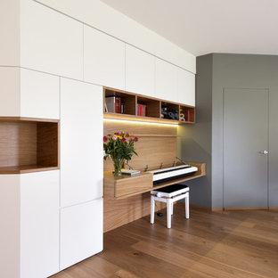 Foto di un grande studio minimalista con libreria, pareti bianche, parquet chiaro e pavimento beige