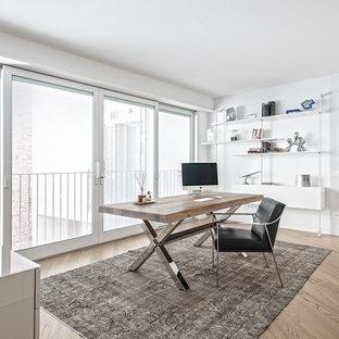 Foto di un grande studio minimal con pareti bianche, pavimento in legno massello medio e scrivania autoportante