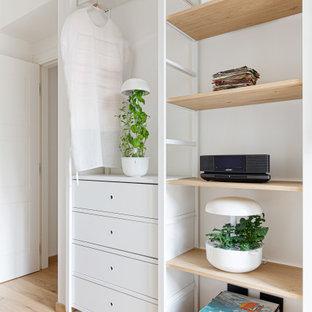 Modelo de despacho escandinavo, pequeño, con paredes blancas, suelo de madera clara y escritorio independiente