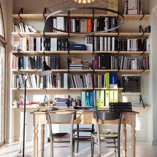 Immagine di uno studio industriale di medie dimensioni con libreria, pareti bianche e scrivania autoportante