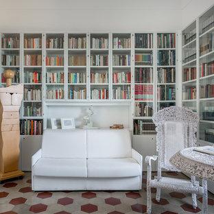 カターニア/パルレモの小さい地中海スタイルのおしゃれなホームオフィス・書斎 (ライブラリー、白い壁、セラミックタイルの床、暖炉なし、自立型机、マルチカラーの床) の写真
