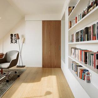 Foto di un grande atelier design con pareti bianche e parquet chiaro