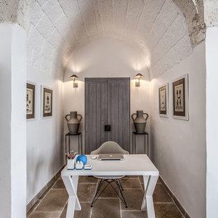 Idee per uno studio mediterraneo con pareti bianche, scrivania autoportante e pavimento marrone