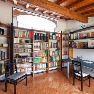 Idee per uno studio mediterraneo con libreria, pareti bianche, scrivania autoportante e pavimento marrone