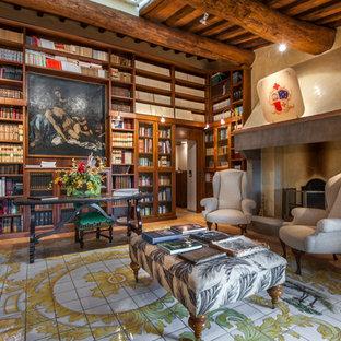 Idee per uno studio tradizionale con libreria, pareti beige, camino classico, cornice del camino in cemento, scrivania autoportante e pavimento multicolore