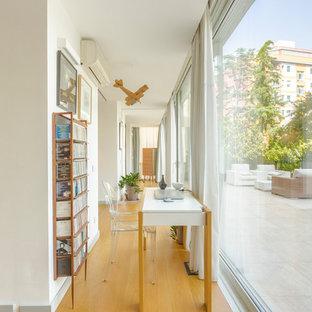 Foto di un grande studio minimal con pareti bianche, pavimento in legno massello medio, scrivania autoportante e pavimento marrone