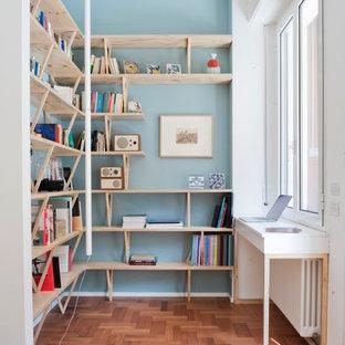 Immagine di uno studio scandinavo di medie dimensioni con pareti blu, pavimento in legno massello medio, libreria, scrivania incassata e pavimento marrone