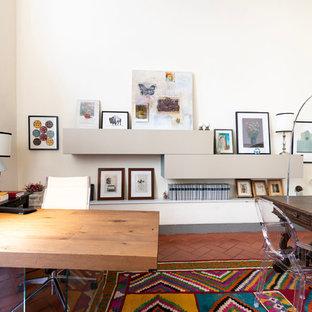 Esempio di un grande ufficio minimalista con pareti bianche, pavimento in terracotta, camino classico, cornice del camino in cemento, scrivania autoportante e pavimento marrone