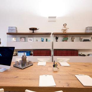 Immagine di un grande ufficio minimalista con pareti bianche, pavimento in terracotta, camino classico, cornice del camino in cemento, scrivania autoportante e pavimento marrone