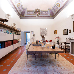 Large modern study in Florence with white walls, terracotta flooring, a standard fireplace, a concrete fireplace surround, a freestanding desk and brown floors.