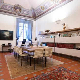 Idee per un grande ufficio minimalista con pareti bianche, pavimento in terracotta, camino classico, cornice del camino in cemento, scrivania autoportante e pavimento marrone
