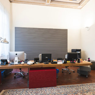 Design ideas for a large modern study in Florence with white walls, terracotta flooring, a freestanding desk and brown floors.
