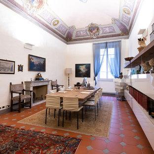 This is an example of a large modern study in Florence with white walls, terracotta flooring, a standard fireplace, a concrete fireplace surround, a freestanding desk and brown floors.