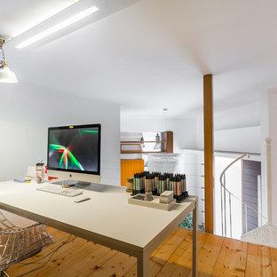 Immagine di un piccolo atelier minimal con pareti bianche, parquet chiaro e scrivania autoportante