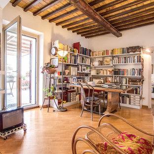 ローマの中サイズのエクレクティックスタイルのおしゃれなホームオフィス・仕事部屋 (白い壁、無垢フローリング、自立型机、ライブラリー、茶色い床) の写真