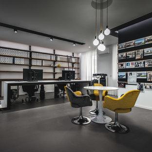 Ispirazione per un atelier industriale di medie dimensioni con pareti bianche, scrivania autoportante, pavimento grigio e pavimento in cemento