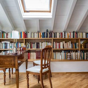 Bild på ett vintage arbetsrum, med ett bibliotek, vita väggar, ett fristående skrivbord, brunt golv och ljust trägolv