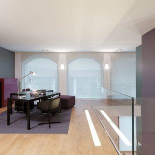Foto di un grande atelier contemporaneo con pareti multicolore, parquet chiaro e scrivania autoportante