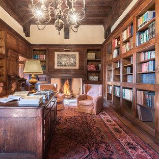 Immagine di un grande studio chic con libreria, pareti bianche, camino classico, cornice del camino in legno, scrivania autoportante, parquet scuro e pavimento marrone