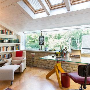 Idee per uno studio mediterraneo con libreria, pavimento in legno massello medio, nessun camino e scrivania autoportante