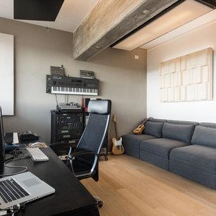 Immagine di un atelier minimal con pareti grigie, parquet chiaro, scrivania autoportante e pavimento beige