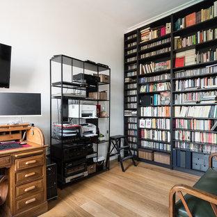 Inspiration för moderna arbetsrum, med ett bibliotek, vita väggar, mellanmörkt trägolv, ett fristående skrivbord och brunt golv