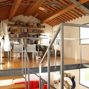 ヴェネツィアの中サイズのモダンスタイルのおしゃれなホームオフィス・書斎 (白い壁、淡色無垢フローリング、ライブラリー、自立型机、黄色い床) の写真