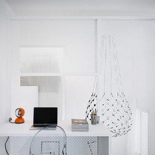Ejemplo de despacho actual, pequeño, con suelo azul, paredes blancas y escritorio empotrado