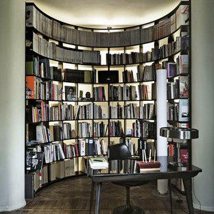 Ispirazione per uno studio minimal con libreria, pavimento in legno massello medio, scrivania autoportante, pavimento marrone e pareti bianche