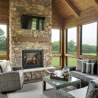 Aménagement d'une très grand véranda classique avec un sol en carrelage de céramique, une cheminée standard, un manteau de cheminée en pierre et un plafond standard.