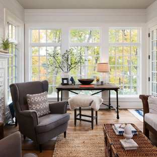 Inspiration for an eclectic medium tone wood floor and brown floor sunroom remodel with a standard fireplace, a brick fireplace and a standard ceiling
