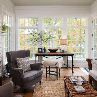 Inspiration för eklektiska uterum, med mellanmörkt trägolv, en standard öppen spis, en spiselkrans i tegelsten, tak och brunt golv