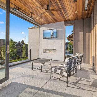 Inspiration för ett mellanstort funkis uterum, med betonggolv, en dubbelsidig öppen spis, en spiselkrans i trä, tak och grått golv