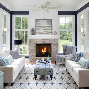 Coastal light wood floor sunroom photo in Minneapolis with a standard fireplace, a stone fireplace and a standard ceiling
