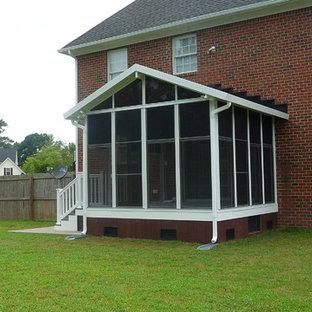 Exemple d'une véranda victorienne de taille moyenne avec un puits de lumière, un sol en carrelage de porcelaine et un sol gris.
