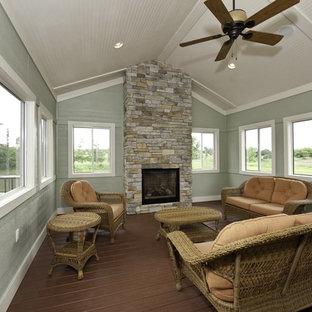 グランドラピッズの大きいおしゃれなサンルーム (濃色無垢フローリング、石材の暖炉まわり、標準型天井、標準型暖炉) の写真