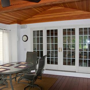 Inredning av ett klassiskt mellanstort uterum, med mellanmörkt trägolv och tak
