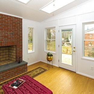 Foto på ett litet vintage uterum, med vinylgolv, en standard öppen spis, en spiselkrans i tegelsten, takfönster och gult golv
