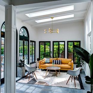 Klassisk inredning av ett mellanstort uterum, med betonggolv, takfönster och grått golv