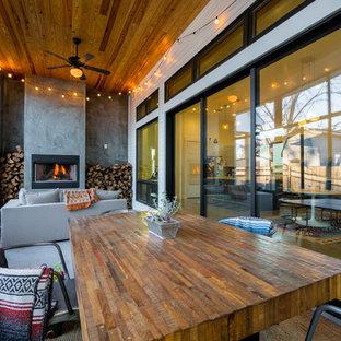 Ispirazione per una veranda design con pavimento in cemento, camino classico e soffitto classico