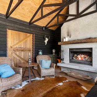 Cette image montre une grand véranda rustique avec un sol en bois brun, un manteau de cheminée en plâtre, une cheminée standard et un sol marron.