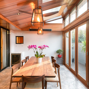 Photo of a transitional sunroom in Sydney with a skylight and grey floor.