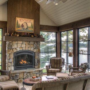 Rustik inredning av ett mellanstort uterum, med mellanmörkt trägolv, en standard öppen spis, en spiselkrans i sten, tak och brunt golv
