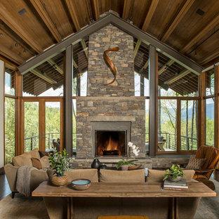 Cette image montre une grand véranda design avec un sol en bois foncé, un manteau de cheminée en pierre, une cheminée double-face, un plafond standard et un sol marron.