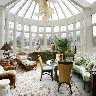 Exemple d'une véranda victorienne de taille moyenne avec un sol en ardoise, aucune cheminée et un plafond en verre.