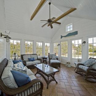 Aménagement d'une véranda bord de mer avec un sol en carreau de terre cuite, un plafond standard et un sol orange.