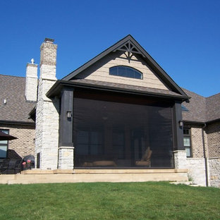 Inredning av ett klassiskt mellanstort uterum, med betonggolv, en dubbelsidig öppen spis, en spiselkrans i sten, tak och grått golv