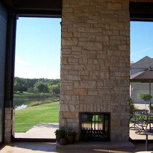 Aménagement d'une véranda classique de taille moyenne avec béton au sol, une cheminée double-face, un manteau de cheminée en pierre, un plafond standard et un sol gris.